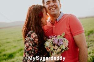 ¿Cómo conversar con una Sugar Baby?: En la imagen vemos a un hombre y una mujer que están teniendo un momento íntimo. Están compartiendo risas y se abrazan. Parece que tienen una muy buena conversación.