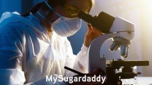 Lo que las mujeres quieren: En la imagen podemos ver a una mujer mirando por un microscopio. Lleva un delantal puesto y una máscara. Parece ser una bióloga.