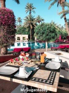 Lo que las mujeres quieren: un desayuno en el jardín con una vista espectacular. Una piscina en el fondo y unas palmeras alrededor. Un estilo de vida magnifico.