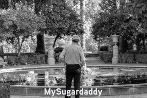 Salir con hombres maduros: La imagen está en blanco y negro. Podemos ver a un hombre mayor de espaldas en un parque. Esta solo y no tiene a nadie. Sin embargo, salir con hombres maduros es la nueva moda.
