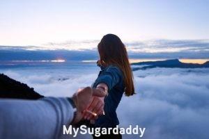 Sugar Baby busca: En la imagen vemos una mujer mirando hacia el horizonte y sosteniendo la mano de su pareja. Simboliza el porvenir, que quiere lograr en su relación con el hombre a su lado.